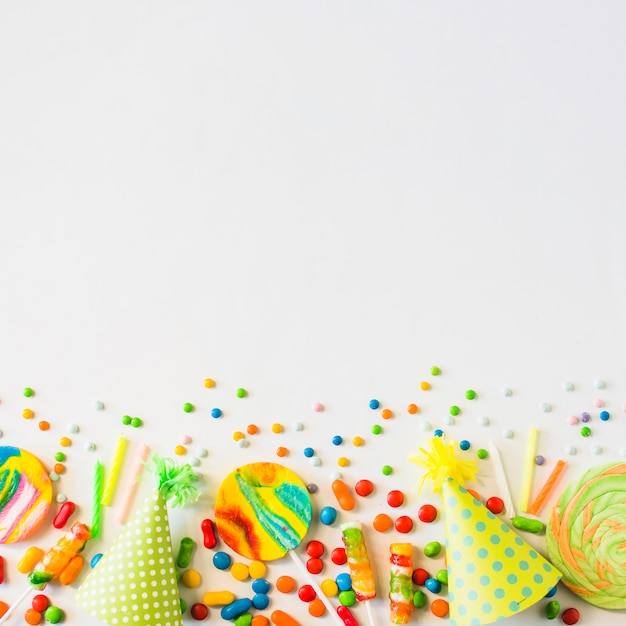 Colorful candies; candles and party hat on white background