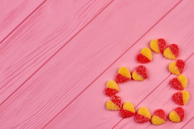 심장 모양을 형성하는 다채로운 사탕. 심장 모양의 나무 배경 복사 공간에 과자 만든 심장. 발렌타인 데이 휴일 인사말 카드.