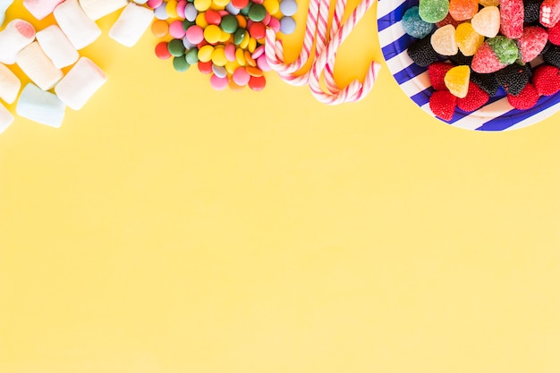 Colorful candies forming the top border on yellow background
