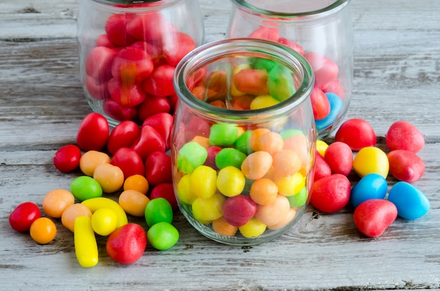 Colorful candies in glass jar and scattered on table