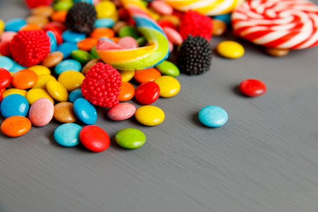 Colorful candies on a grey wooden table