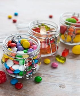 Красочные конфеты, желе и мармелад в банках на столе