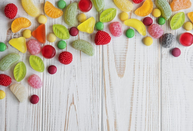 Colorful candies, jelly and marmalade on white wooden surface with copy space