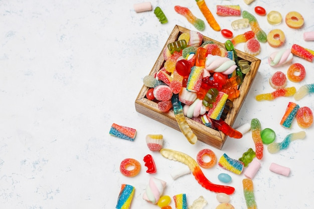 다채로운 사탕, 젤리, 밝은 표면에 마시 멜로. 복사 공간이있는 평면도