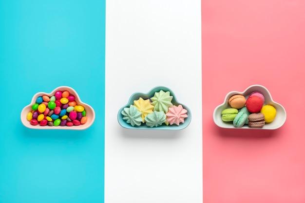 カラフルなキャンディー-ロリポップ、メレンゲ、ピンク、白で隔離の雲の形をしたボウルのマカロン