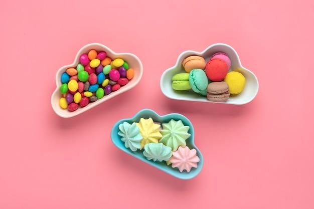 カラフルなキャンディー-ロリポップ、メレンゲ、ピンクで分離された雲の形をしたボウルのマカロン