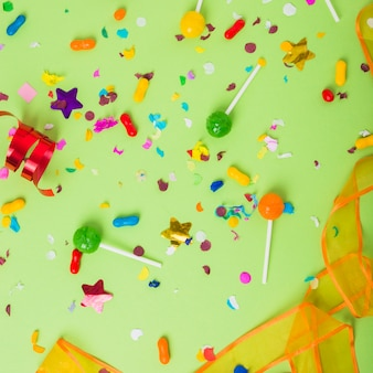 Colorful candies and lollipops with confetti and curled streamer on green background