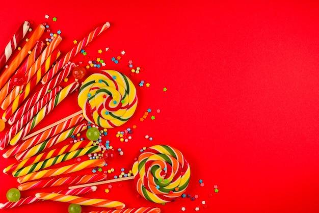 Красочные конфеты на красном фоне. леденец на палочке. вид сверху. скопируйте пространство.