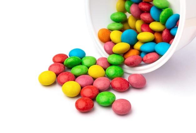 Красочные конфеты из открытого контейнера, изолированные на белой поверхности