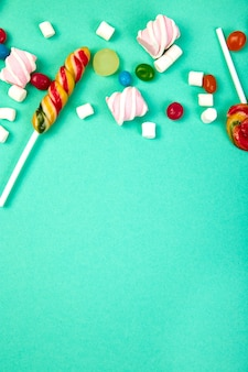 Colorful candies on pastel turquoise.