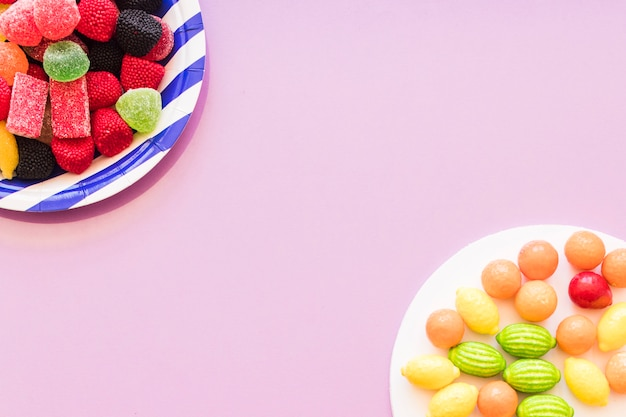 Colorful candies plate on the pink background corner