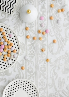 Colorful candies on polkadot plates over the floral tablecloth
