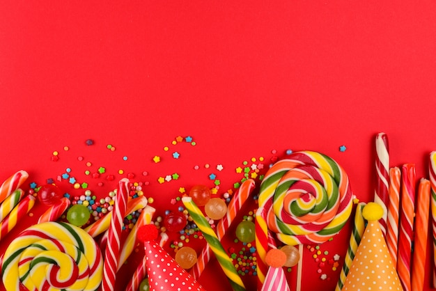 Colorful candies on a red  background. lollipop. top view. copy space.