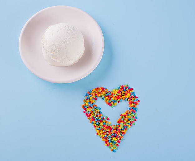 Colorful candies in the shape of a heart and ice cream on the blue background.