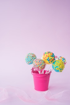 Colorful candies in a small bucket on a pink background. space for text. Premium Photo