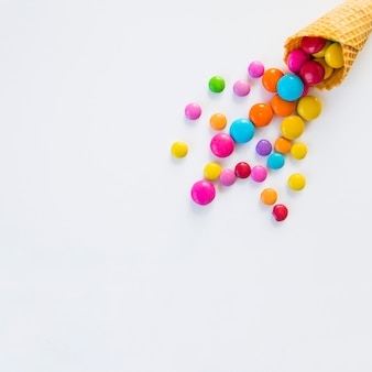 Colorful candies spilled from a waffle cone on white background