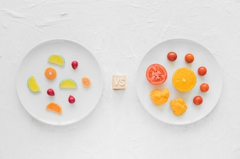Colorful candies versus fresh vegetables on white plate over background