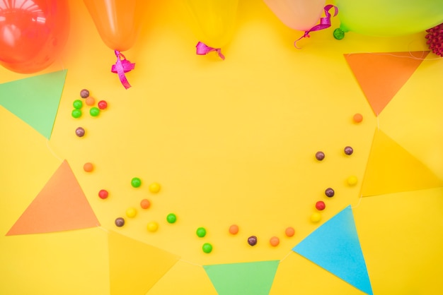 Colorful candies with bunting and balloons on yellow background