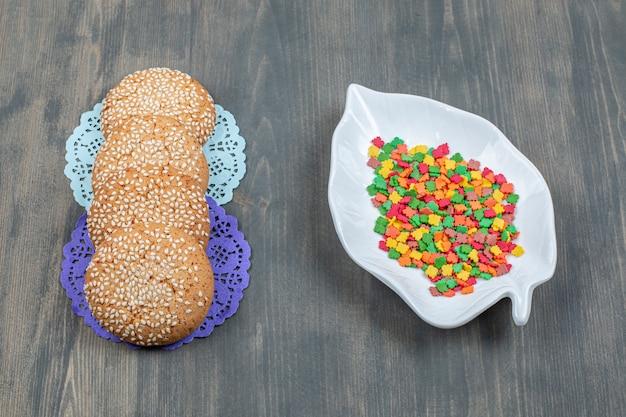 木製のテーブルにおいしいクッキーとカラフルなキャンディー