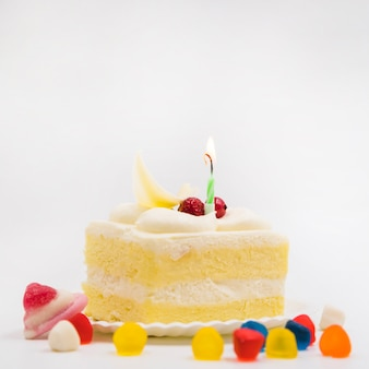 Colorful candies with slice of cake on plate against white background