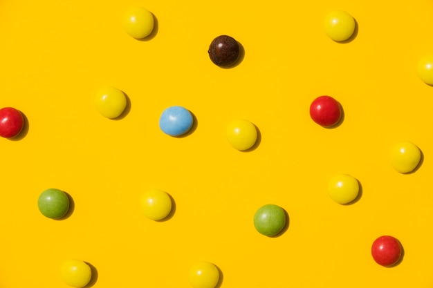 Colorful candies on yellow backdrop