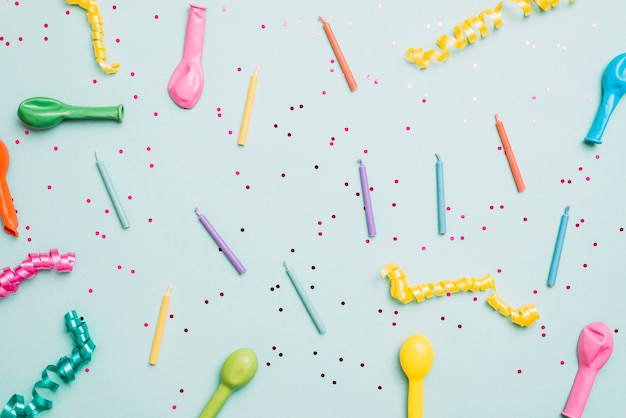 Colorful candles; deflated balloons and streamers on blue background