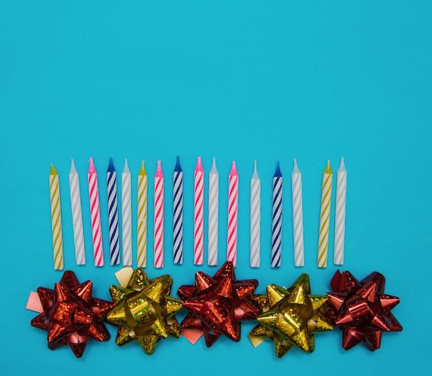 バースデーケーキ用のカラフルなキャンドルと青い背景のパッケージ用の弓