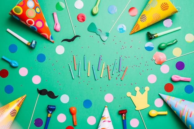 Разноцветные свечи в окружении колпаков; надувные шарики; день рождения реквизит и конфетти на зеленом фоне