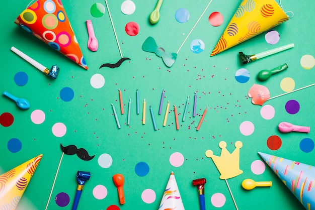 Colorful candles surrounded with party hats; balloons; birthday props and confetti on green background