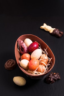 Colorful candy and chocolate easter eggs on black slate plate with copy space