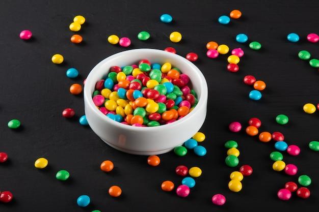 다채로운 캔디. 다채로운 과자 배경입니다. 검정색 배경.
