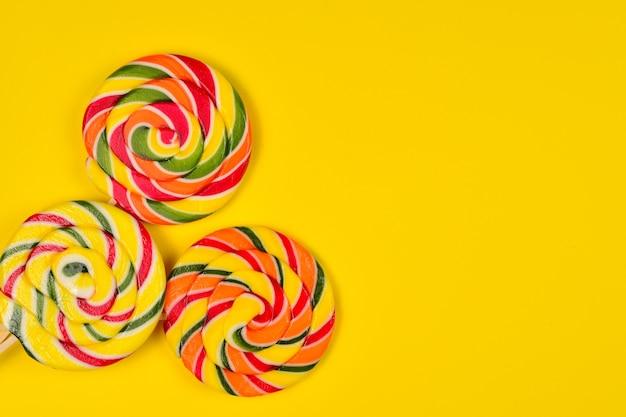 Красочные конфеты на желтом фоне. леденец на палочке. вид сверху. скопируйте пространство.