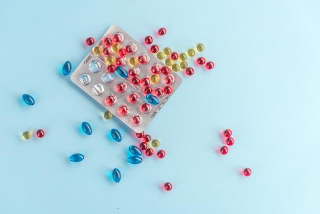 Разноцветные капсулы и таблетки упакованы в блистеры