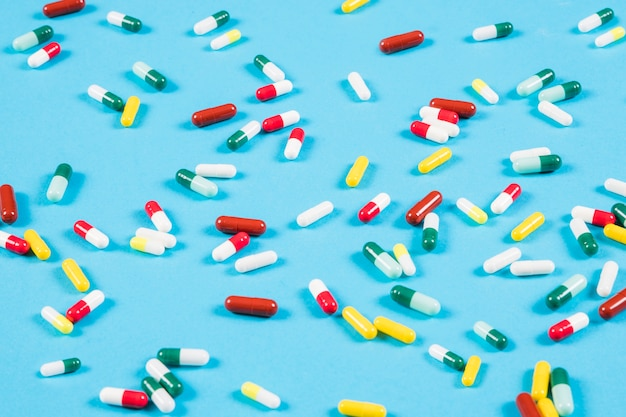Colorful capsules spread on blue background