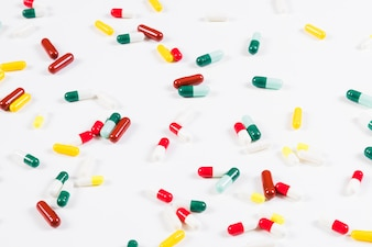 Colorful capsules spread on white background