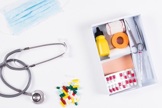 Colorful capsules; stethoscope and mask with first aid kits on white background