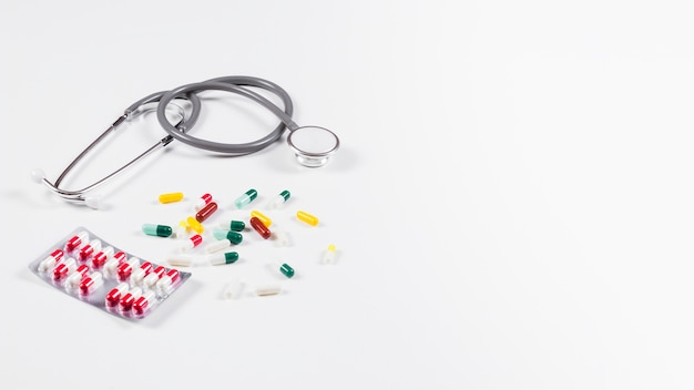 Colorful capsules and stethoscope on white background