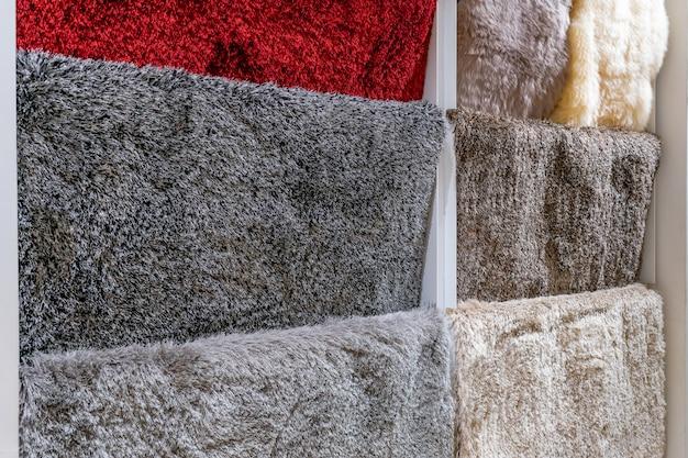Разноцветные образцы ковров в магазине магазина