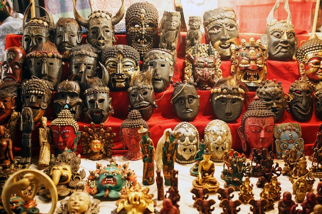 Продаются разноцветные резные маски, на стене висят разноцветные маски разных духов.