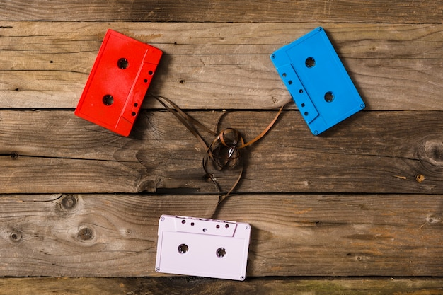Colorful cassette tapes with tangled tape on wooden background