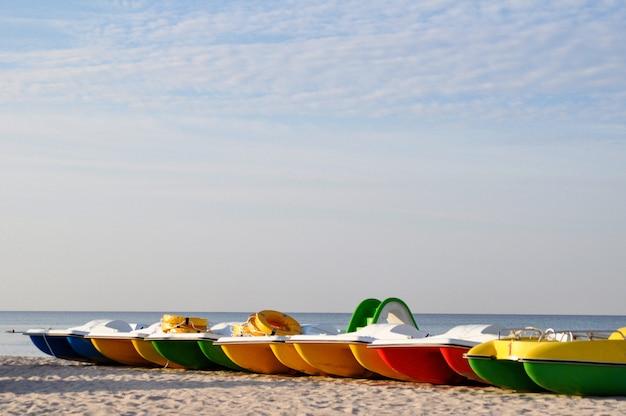 Colorful catamarans near the sea shore on a deserted beach at dawn