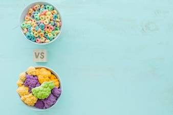 Colorful cauliflower versus cereals in bowls over blue backdrop