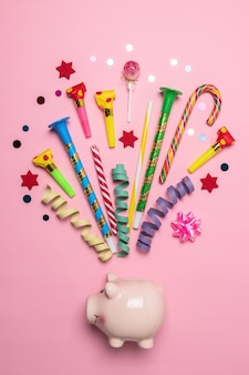 Colorful celebration background with piggy bank, various party confetti, streamers and decoration.