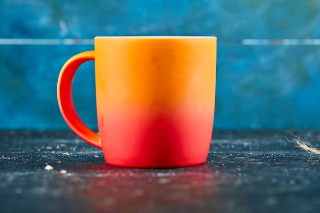 Colorful ceramic mug isolated on blue desk.