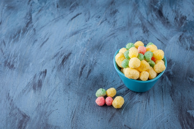 Colorful cereal balls placed in a blue bowl .