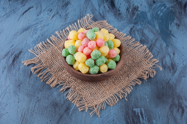 Colorful cereal balls placed in a wooden bowl .