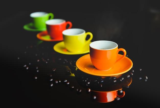 暗いテーブルとコーヒー豆にエスプレッソコーヒーの煙が入ったカラフルなセレミックコーヒーカップ。