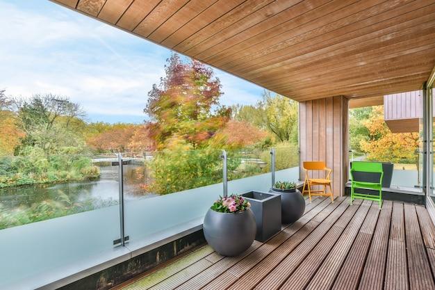 川や秋の木々に対するガラス柵の近くのテラスに置かれた花とカラフルな椅子とポット