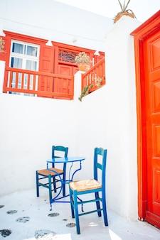 미코노스 섬, 그리스, 유럽에 하얀 집들이있는 전형적인 그리스 전통 마을의 거리에 다채로운 의자와 테이블