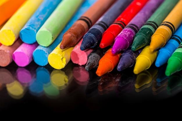 다채로운 분필 및 연필 검은 배경에 고립입니다.